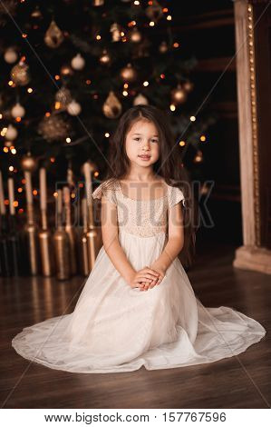 Cute baby girl 4-5 year old wearing stylish dress sitting under Christmas tree with lights in room. Looking at camera. Holiday season.
