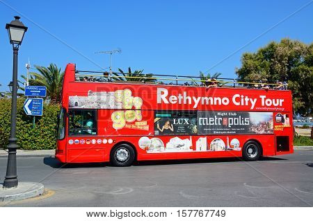 RETHYMNO, CRETE - SEPTEMBER 15, 2016 - Tourists aboard a red open topped Rethymno City Tour bus Rethymno Crete Greece Europe, September 15, 2016.