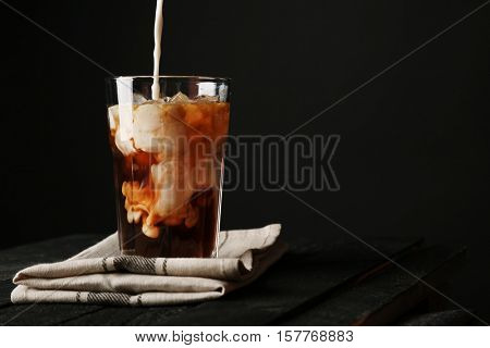 Pouring cream into a glass with iced coffee on napkin and black background