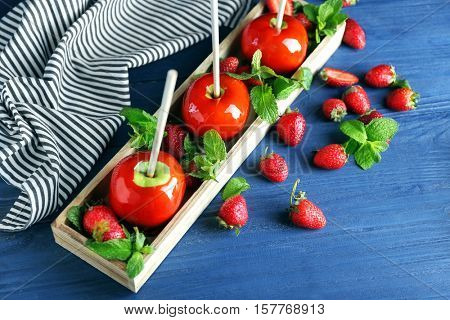 Candy apples with strawberry on wooden table closeup