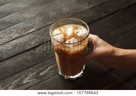 Female hand holding glass of iced coffee on wooden table