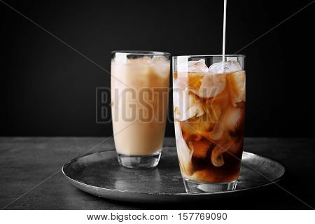 Pouring milk in iced coffee on grey background