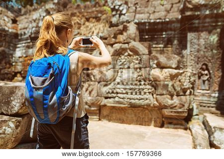 Tourist Taking Photo Of Bas-reliefs In Temple. Angkor, Cambodia