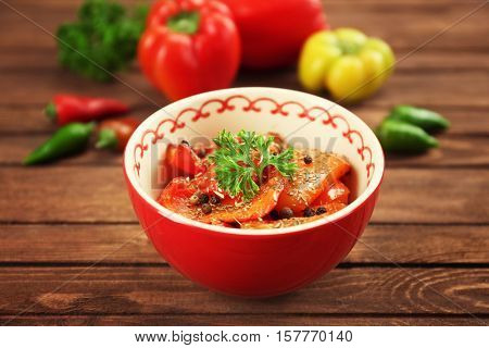 Grilled bell pepper in bowl and fresh vegetables on wooden background