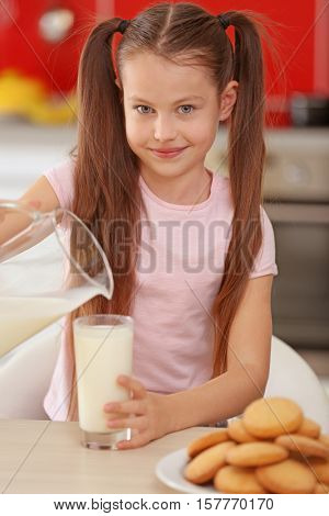 Cute little girl pouring fresh milk into glass at kitchen