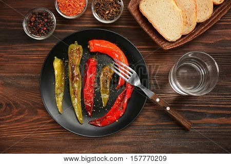 Grilled chili pepper with spices and bread on wooden background, top view