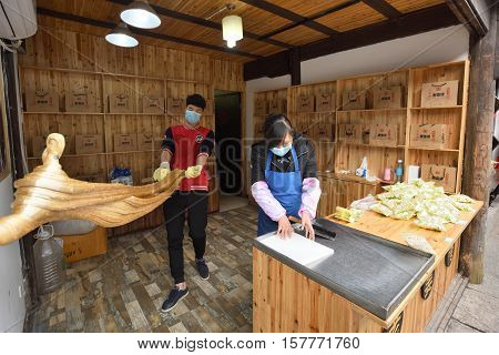 WUZHEN CHINA - MARCH 24: Unidentified Chinese people making traditional confectionery products on March 24 2016 in Wuzhen China. Wuzhen is a historic scenic town located in northern Zhejiang Province China