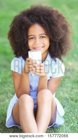 Pretty African-American girl drinking milk and sitting on the lawn