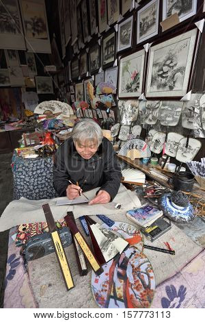 WUZHEN CHINA - MARCH 24: Unidentified Chinese artist creates traditional souvenirs on March 24 2016 in Wuzhen China. Wuzhen is a historic scenic town located in northern Zhejiang Province China