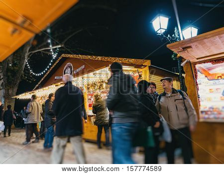 STRASBOURG FRANCE - DEC 6 2015: Adults childrens grandparents and happy people walking during Christmas Market admiring market stall buying food presents and toys