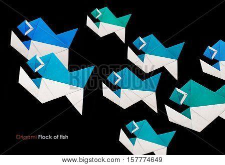 Origami paper piranha fish flock on a black background