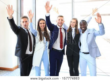 Portrait of successful business group waving hands in office