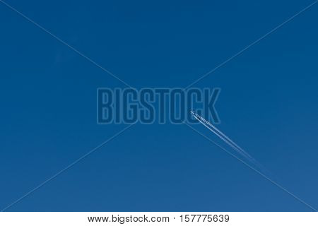 plane with contrails in a clear blue sky