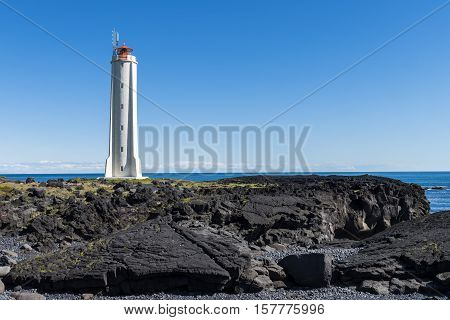 White lighthouse at Londrangar on Snaefellnes Westfjords on Iceland with volcanic lava rocks and ocean