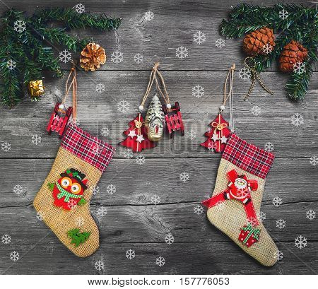 Two Christmas socks for presents. Christmas decoration stocking and toys hanging over gray rustic wooden background. The socks of burlap Christmas sweets gifts cakes. Christmas snowflakes. Top view