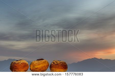 Sweet donuts of Hanukkah holiday against the colorful background of cloudscape at sunrise, selective focus applied