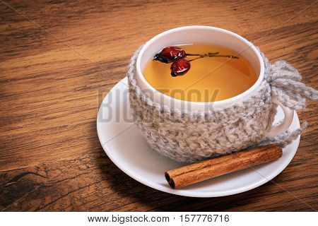 Cup of herbal tea with briar on a wood background