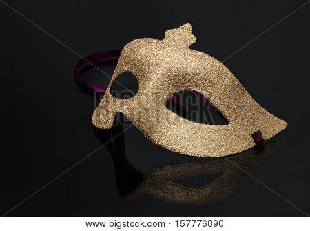 Carnaval golden mask on a black mirror background