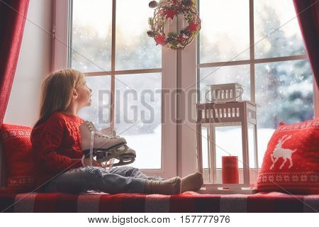 Merry Christmas and happy holidays! Cute little girl sitting by the window and looking at the winter forest. Room decorated on Christmas. Kid enjoys the snow and dreams to skate.