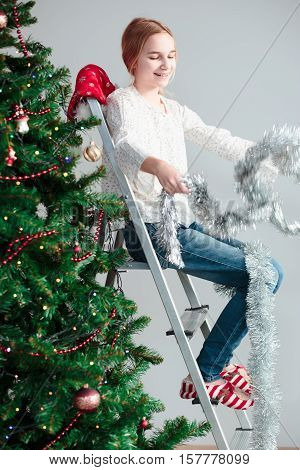 Young girl unwrapping Christmas decoration sitting on a ladder