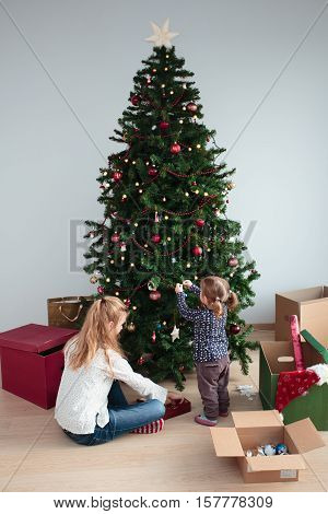 Young girl and her little sister decorating Christmas tree at home