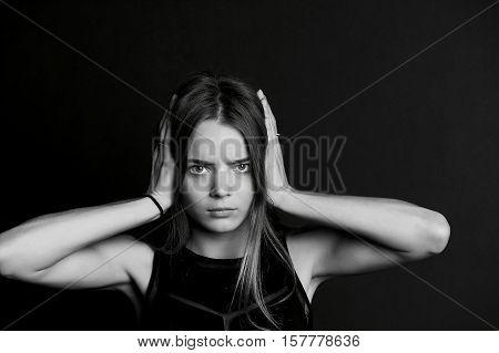 Hear no evil. The girl closes the hands. Long hair