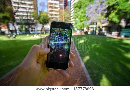 Buenos Aires, Argentina - Nov 11, 2016: Apple iPhone 5c held in one hand showing its screen with Pokemon Go application. Park on the background.