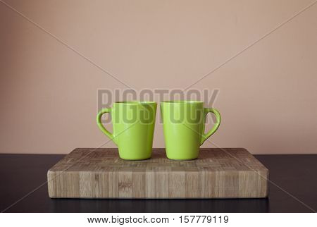 two green cups on wooden cutting board with touching handles, twins cups