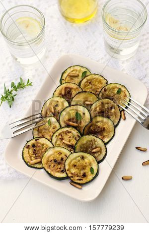 Antipasto of courgette zucchini with olive oil pine nuts and herbs