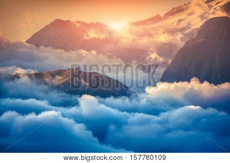 View of the foggy Val di Fassa valley with passo Sella. National Park. Dolomites South Tyrol. Location Canazei Campitello Mazzin. Italy Europe. Retro style.