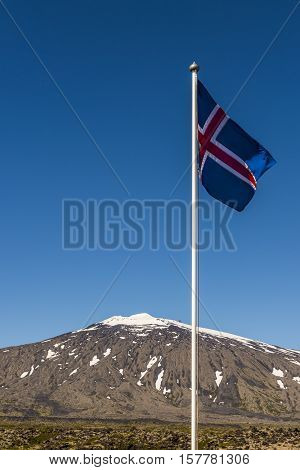 Mountain Snaefellsjokull with snow and ice in National Park on Westfjords and Icelandic Flag in front.
