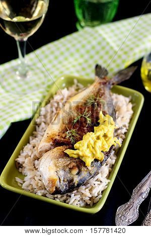 Pan fried breaded gilt-head bream with rice and onion sauce