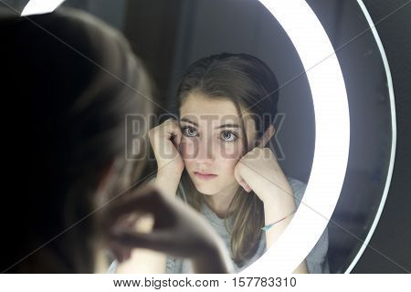 Portrait Of Teenage Looking In A Mirror