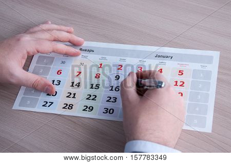 calendar sheet with encircled date and hand with pen