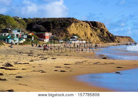 November 21, 2016 in Laguna Beach, CA:  People relaxing on the sandy beach and swimming in the ocean with bluffs and rustic cottages beyond taken at Crystal Cove Beach where people can relax, swim, and stay in cottages in Laguna Beach, CA
