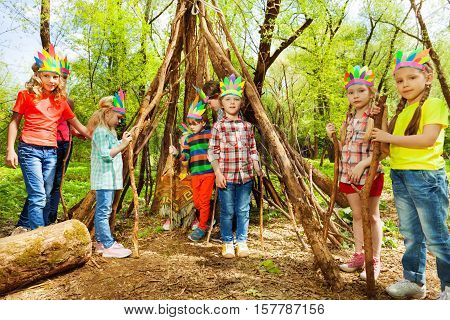 Happy boys and girls in Injun's headdresses, building wigwam of branches in the forest poster