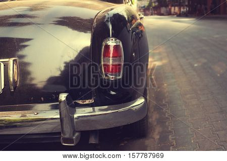 Rear view of classic car parked on road in urban - vintage retro color effect styles