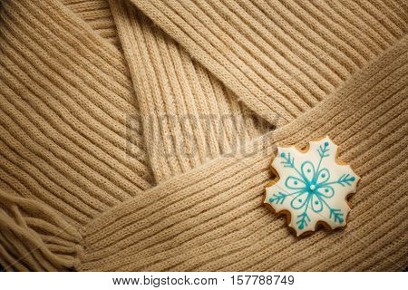 Beautiful tasty homemade christmas ginger biscuit cookie with snowflake pattern covered by white and blue icing lays on beige woollen scarf background. Copyspace.