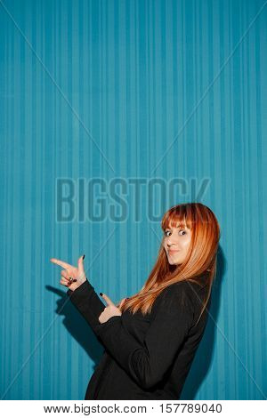 Portrait of young woman with shocked facial expression over blue studio background pointing on the left