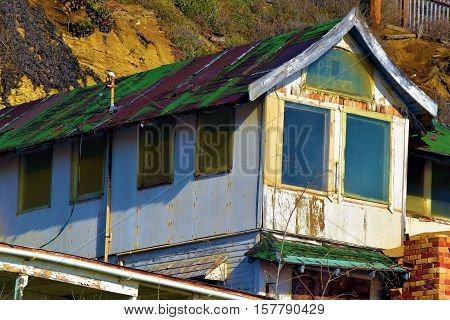 Abandoned dilapidated home beside a mountain which needs remodeling