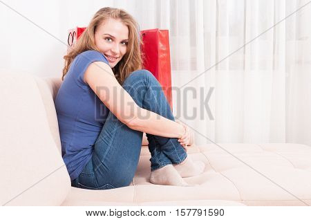Woman Sitting On Couch Feeling Comfy And Smiling