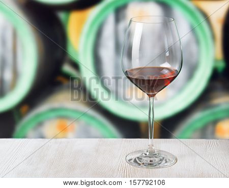 Glass Of Wine And Wooden Barrels In Winery