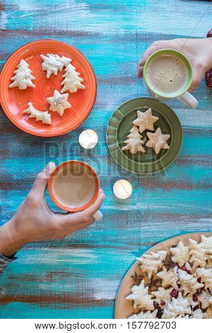 Couple drinking coffee with christmas cookies sitting at an old wooden table. Male and female hands holding cups of coffee over wooden background. Meeting on the winter holidays.