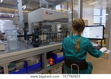 ST. PETERSBURG, RUSSIA - NOVEMBER 16, 2016: Researcher at work with automated station of selection of cultivation condition in the High-Throughput Biotechnology Laboratory of BIOCAD