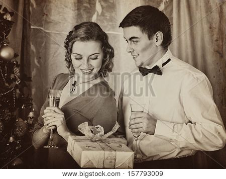 Old photo on yellow paper. Black and white retro. Young people decoration Christmas tree. Girl drink champagne. Man give gift box.