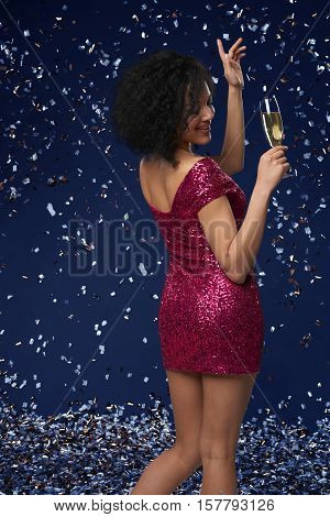Party, drinks, holidays and celebration concept. Happy young mixed race woman in fancy dress with sequins and confetti at party with glass of champagne