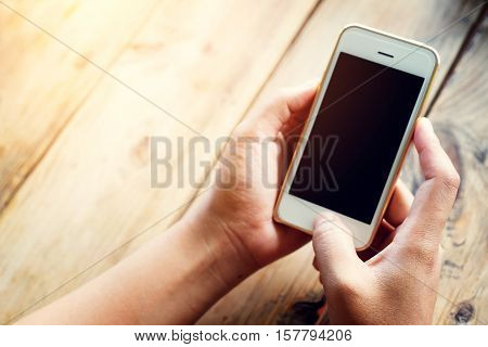 Hand of beautiful young hipster woman using smart phone in coffee shop female watching her cell telephone while relaxing in cafe during free time.