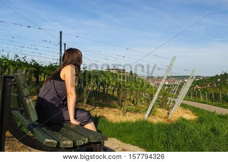 a happy girl on bench relaxing with a view to grape field landcape and the Festung or fort Marienberg in background