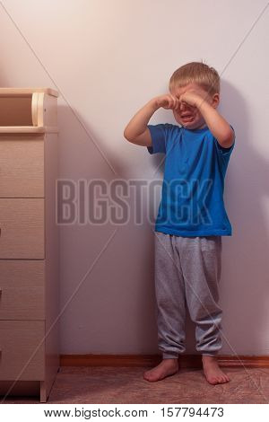 Crying boy staying in corner for punishment. Child abuse.