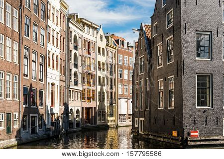 Amsterdam Netherlands - August 1 2016: Amsterdam cityscape canal houses in Red Light District a blue sky day